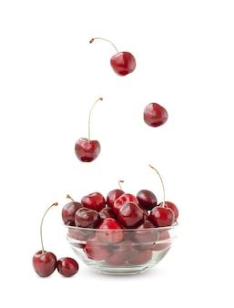 Soczyste wiśnie lewitują w powietrzu i opadają na talerz. wiśnia na białym tle.