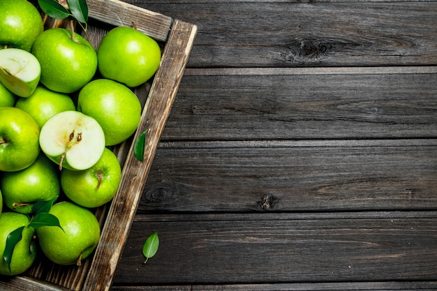 Soczyste zielone jabłka i plasterki jabłka w drewnianym pudełku. na ciemnej drewnianej powierzchni.