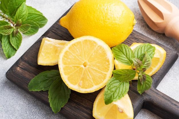 Soczyste żółte cytryny w całości, pokrojone w świeże liście mięty