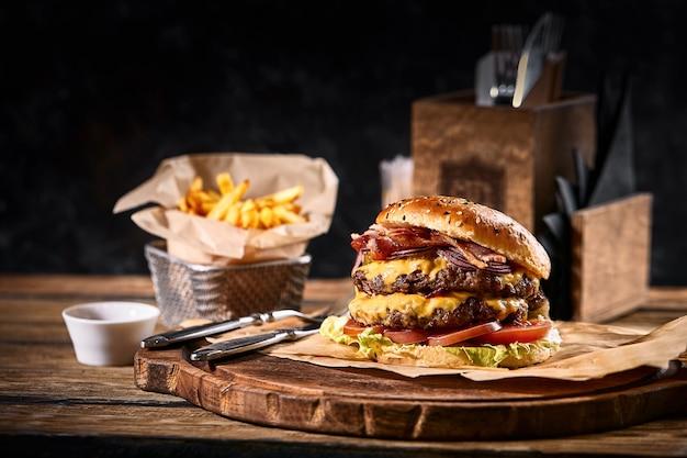 Soczysty amerykański burger z dwoma pasztecikami wołowymi i frytkami