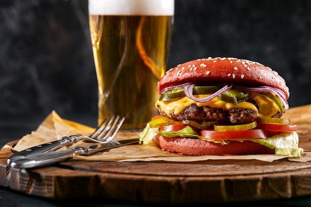 Soczysty burger, frytki, sosy i kufel zimnego piwa na ciemnym drewnianym tle