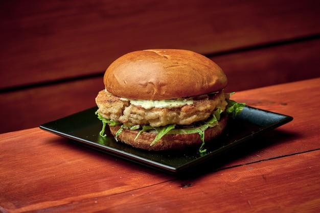 Soczysty burger rybny z sałatką, serem, pomidorem i sosem. na talerzu z frytkami. drewniane tło