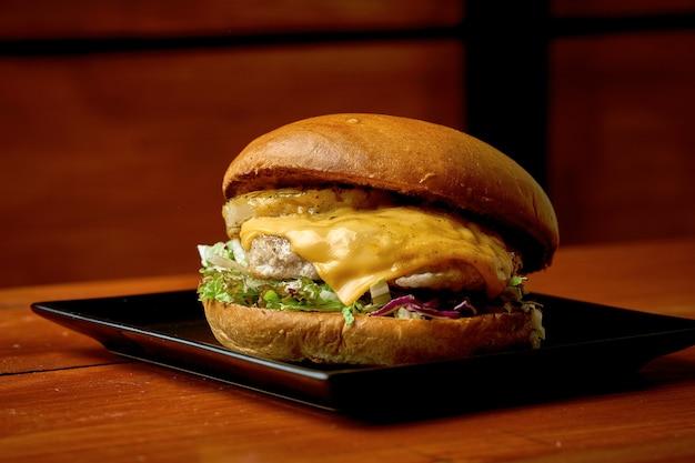 Soczysty burger wieprzowy z sałatką, ananasem. na talerzu z frytkami. drewniane tło