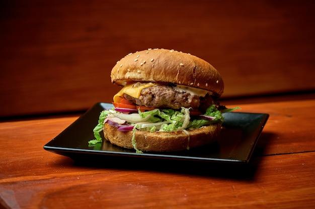 Soczysty burger wołowy z sałatką, serem, pomidorem i sosem. na talerzu z frytkami. drewniane tło