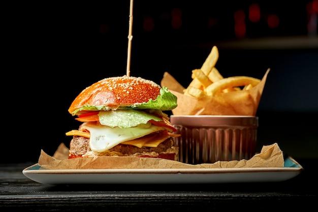 Soczysty burger wołowy z sałatką, serem, pomidorem, jajkiem i sosem. na talerzu z frytkami. drewniane tło