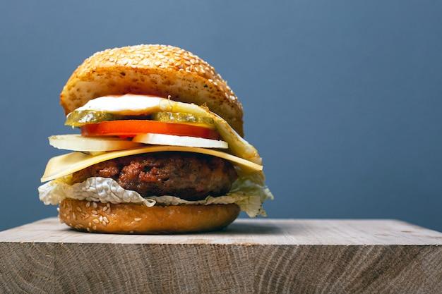 Soczysty burger z kotletem, serem i warzywami na szarym tle z miejsca kopiowania. podwójny cheeseburger na drewnianej desce.