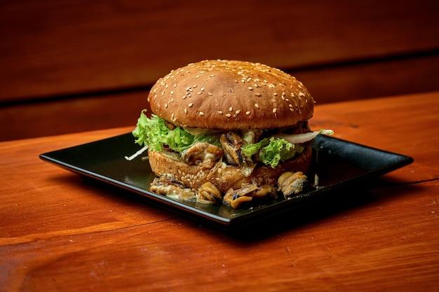Soczysty burger z małżami z surówką i sosem. na talerzu z frytkami. drewniane tło