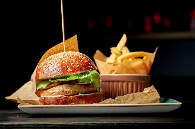 Soczysty burger z sałatką, pomidorami i ogórkami, z indykiem. na talerzu z frytkami. ciemne tło