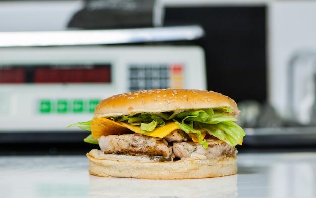 Soczysty cheeseburger na tle wagi kuchennej. niewyraźne tło