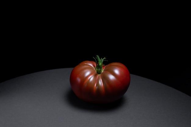 Soczysty czerwony pomidor na białym tle na czarnym tle,