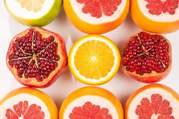 Soczysty grejpfrut, pomarańcza, granat, cytrusowe słodycze na białym tle.