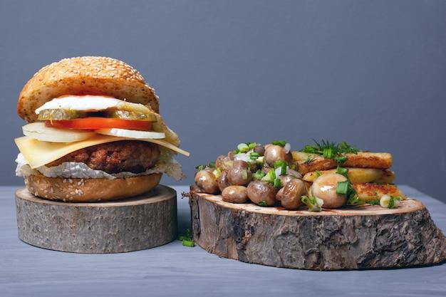 Soczysty gruby burger, smażone ziemniaki i grzyby z ziołami na drewnianych tacach na szarym tle. ciekawe i niecodzienne podawanie fast foodów.