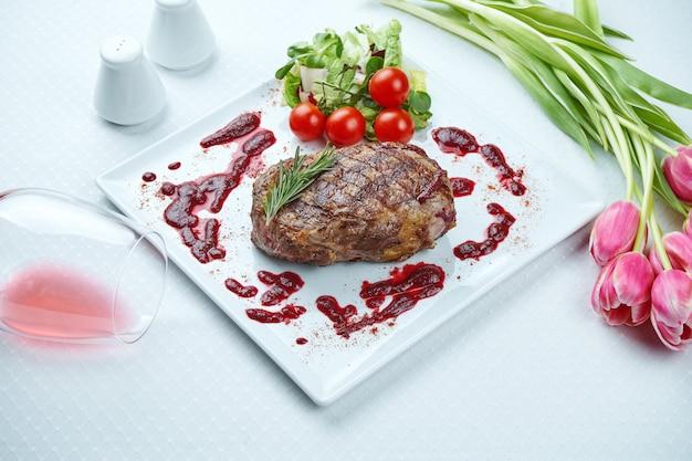 Soczysty i przepyszny grillowany stek ribeye z pikantnym masłem na białym talerzu z dodatkiem warzyw.