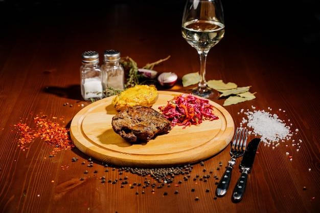 Soczysty kawałek smażonego mięsa leży na desce do krojenia na drewnianym stole. widok z góry