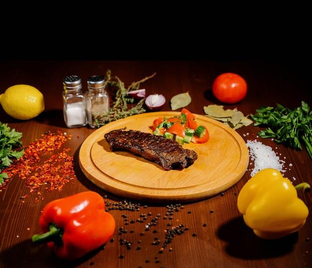 Soczysty kawałek smażonego mięsa leży na desce do krojenia na drewnianym stole.