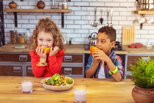 Soczysty owoc. śliczna dziewczyna z kręconymi włosami je grejpfruta i patrzy prosto w kamerę