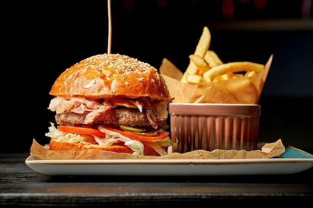 Soczysty podwójny burger wołowy z sałatką, pomidorami i ogórkami. na talerzu z frytkami. ciemne tło