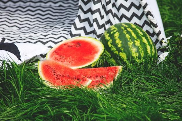 Soczysty pokrojony czerwony arbuz na zielonym trawniku na tle szmacianego namiotu