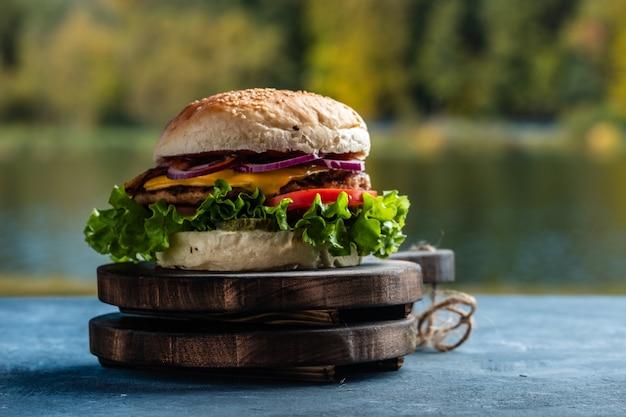 Soczysty smaczny cheeseburger z wołowiną, sałatą, marynatami, pomidorami i krążkami cebuli na drewnianym stole. klasyczne jedzenie uliczne - burger z grilla