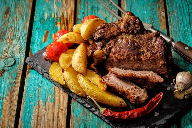 Soczysty stek, dobrze zrobiona wołowina z ziemniakami i pomidorami