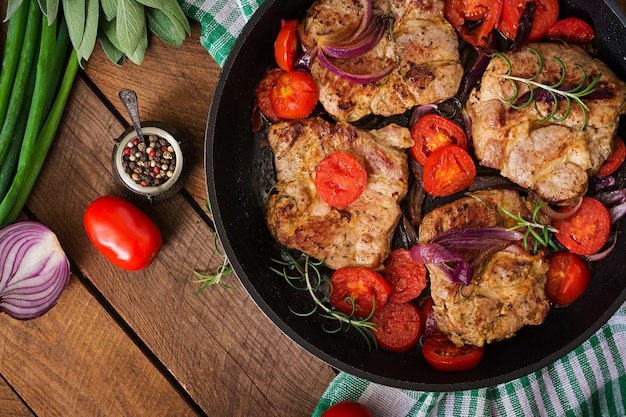 Soczysty stek wieprzowy z rozmarynem i pomidorami na patelni.