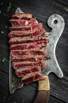 Soczysty stek wołowy nad nożem rzeźniczym. tło przepis żywności. zamknij obraz pionowy, miejsce na tekst