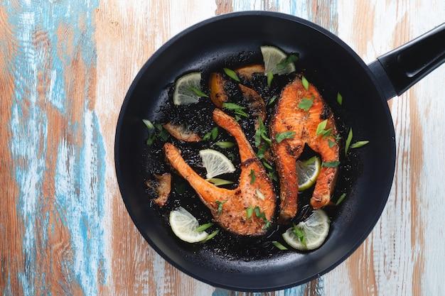 Soczysty stek z łososia z grilla z cytryną, przyprawami i limonką na patelni na jasnym drewnianym stole. pysznie ugotowany filet z łososia