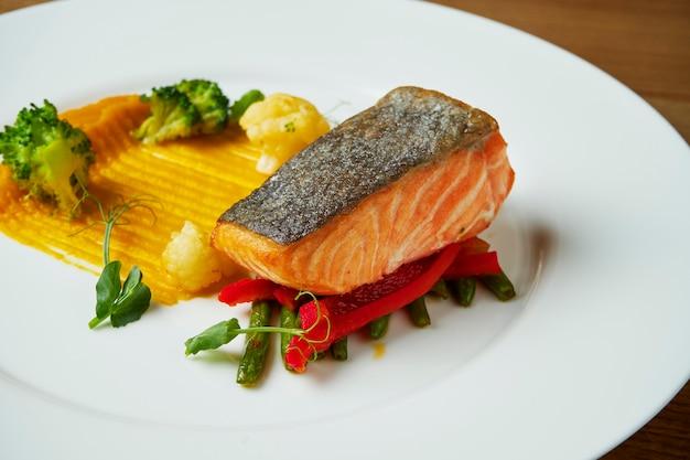 Soczysty stek z pieczonego łososia na białym talerzu z przystawką puree ziemniaczanego. szparagi i brokuły. stół z drewna. zamknij się na smaczne owoce morza w restauracji