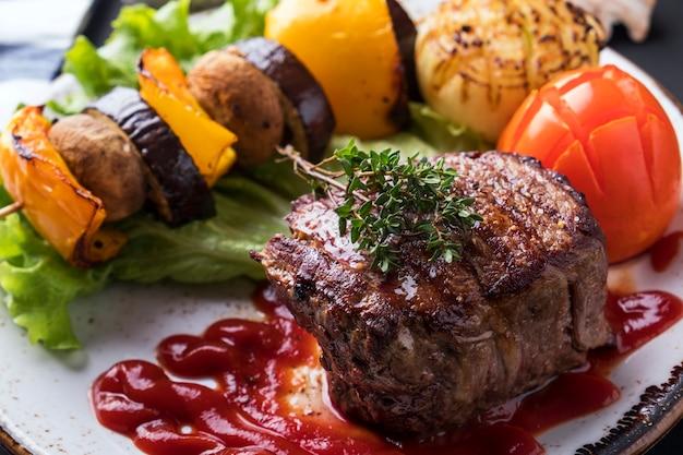 Soczysty stek z średniej wielkości wołowiny z czerwonym sosem i grillowanymi warzywami