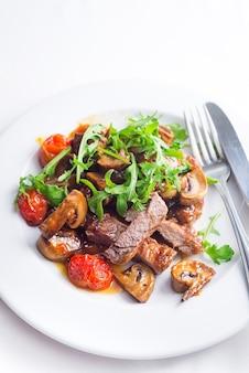 Soczysty stek z średnio rzadkiej wołowiny z rukolą i grillowanymi warzywami. widok z góry