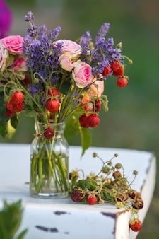 Soczysty świeży bukiet truskawek, lawendy i róż stoi na białym krześle w słoiku z wodą. pyszne jagody i aromatyczne zioła zebrane w ogrodzie i lesie