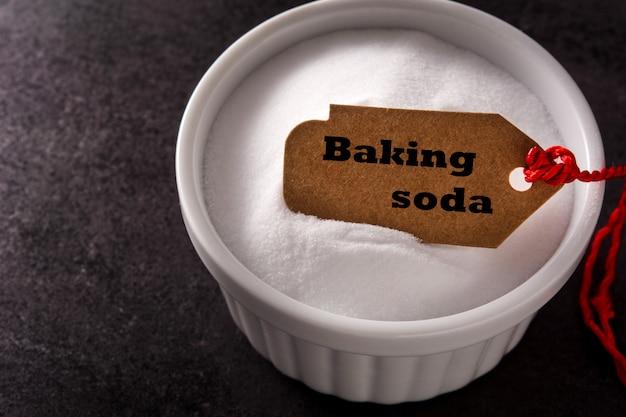 Soda oczyszczona w białej misce na czarno