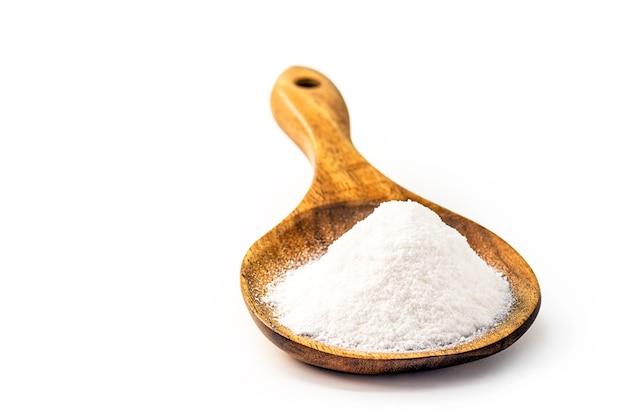 Soda oczyszczona w drewnianą łyżką na białym tle
