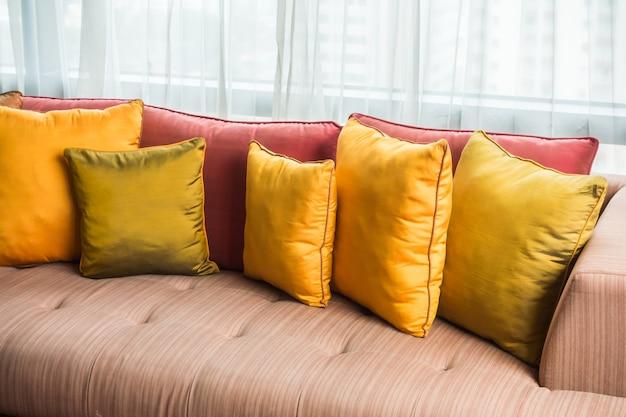 Sofa z poduszkami i białe zasłony tle