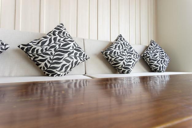 Sofa z poduszkami. widoczny jest również stół.