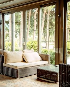 Sofa zewnętrzna z beżowymi poduszkami i stolikiem kawowym przed oknem restauracji