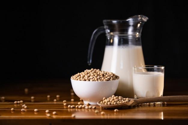 Soi mleko gorący i soje na drewnianym stołowym tle