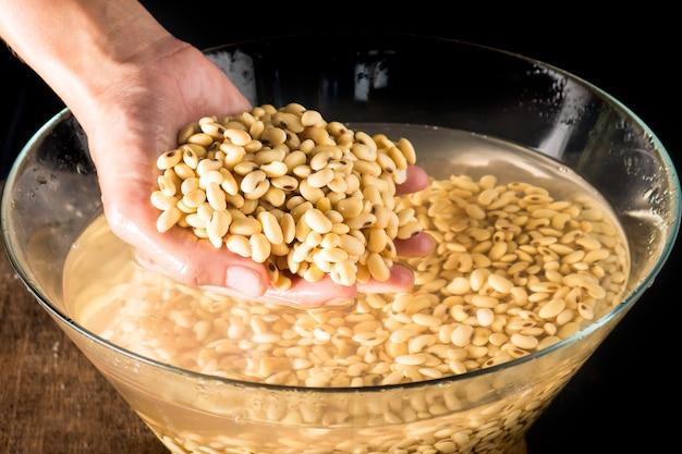Soja lub glicyna w ręku i moczyć w wodzie 3 godziny, aby przygotować mleko sojowe.