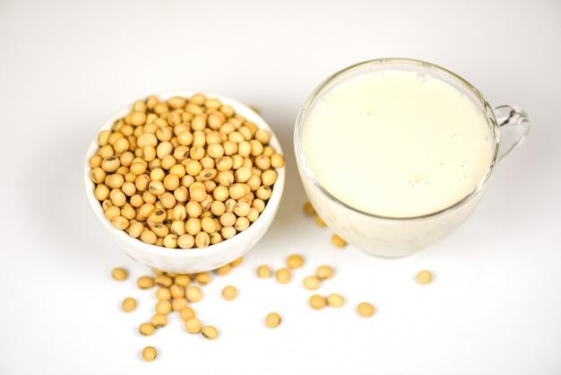 Soja w misce i mleko sojowe w szkle na białym szarym zdrowa dieta mleczna i naturalne białko fasoli