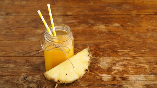 Sok ananasowy na drewnianym tle. szklany słoik z sokiem i plasterkiem świeżego ananasa. egzotyczne owoce i zdrowy sok z witaminami