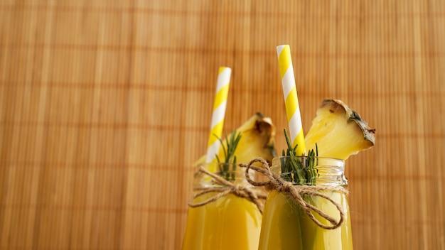 Sok ananasowy w małej butelce. plastry ananasa zdobią napój. sok na drewnianym bambusowym tle. papierowe słomki w napoju
