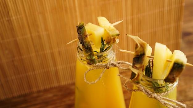 Sok ananasowy w małej butelce. plastry ananasa zdobią napój. sok na drewnianym tle