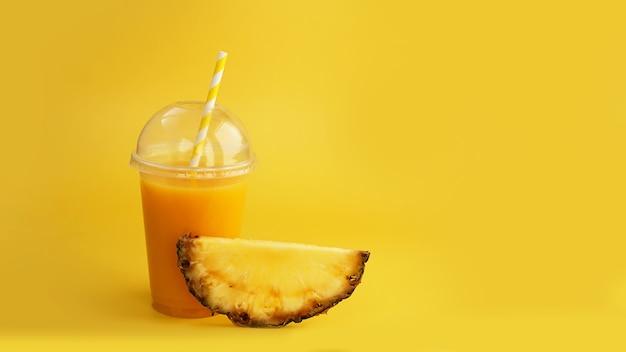 Sok ananasowy w plastikowym kubku na żółtym tle. sok tropikalny - letni baner