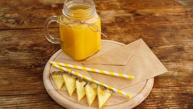 Sok ananasowy w szklanym słoju na drewnianym tle. koperta z listem na drewnianej desce. poranna nuta i śniadanie owocowe