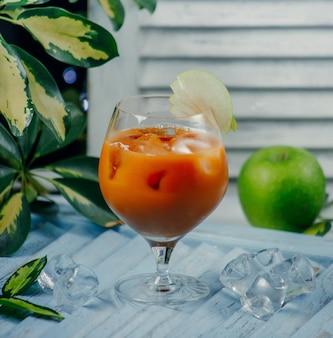 Sok brzoskwiniowy w szklance z kostkami lodu i plasterkami jabłka