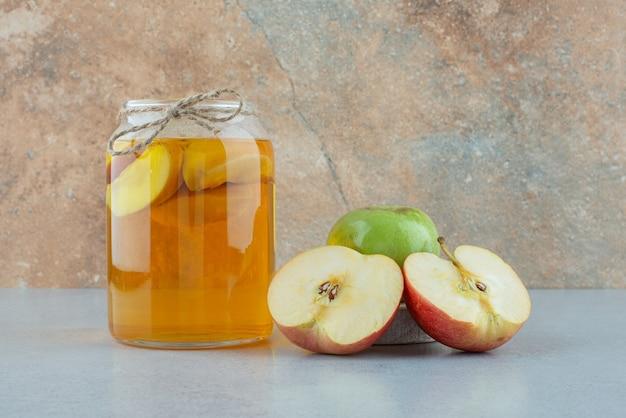 Sok jabłkowy i świeże jabłka na niebieskim tle. zdjęcie wysokiej jakości