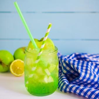 Sok jabłkowy podawany w szklanym słoju z kawałkami jabłka