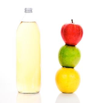 Sok jabłkowy w szklanej butelce i trzy dojrzałe jabłka