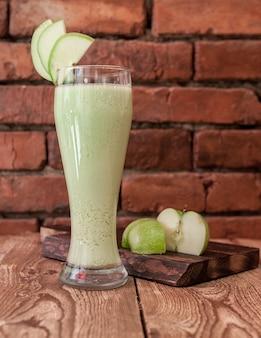 Sok jabłkowy z boku z plasterkami jabłka i drewnianą deską w szkle