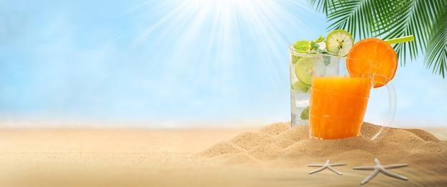 Sok pomarańczowy i napój mojito, pusty piasek z kapeluszem i napojem mojito na krajobrazowej plaży rozmazane tło